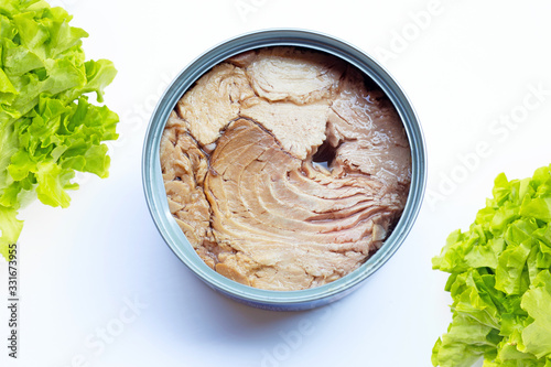 Photo Canned tuna fish  with green oak leaves on white
