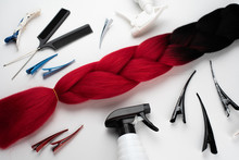 Kanekalon Two- Color-artificial Hair Ombre Red And Black For Braiding Braids, Lying On A White Background Next To Accessories For Braiding Braids