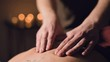 Young male massage therapist is doing finger massage of a woman back with a tattoo in a massage room with dim light on the background of candles. Low key premium massage concept