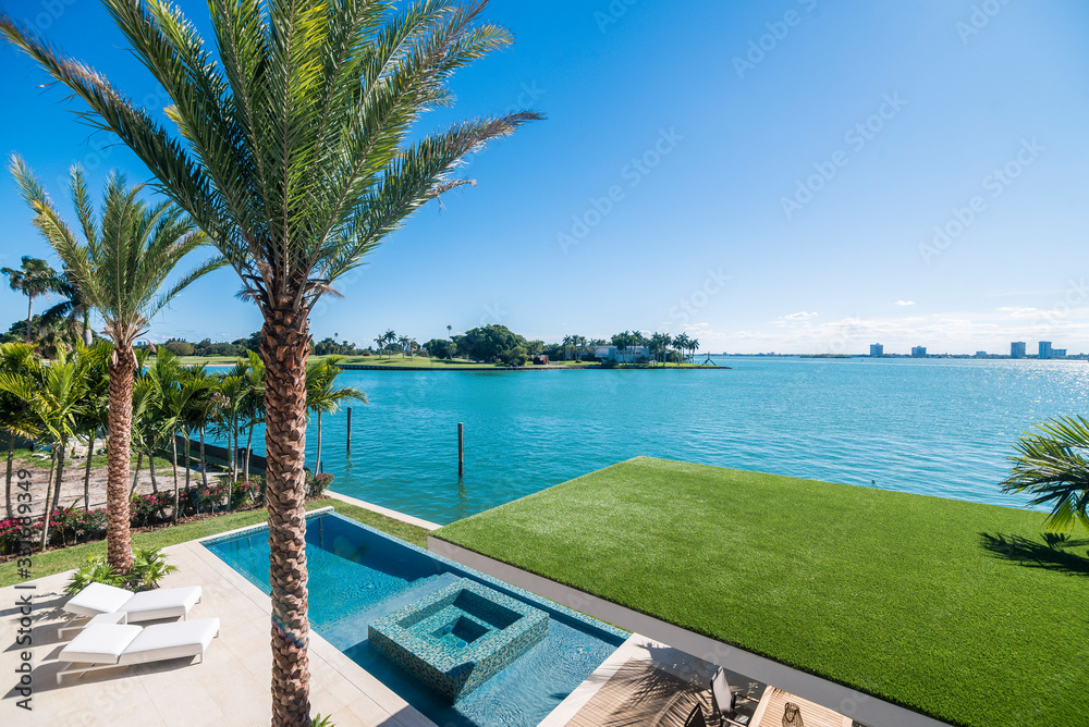 Fototapeta View of a nice pool and waterfront from terrace of a luxury home in Miami