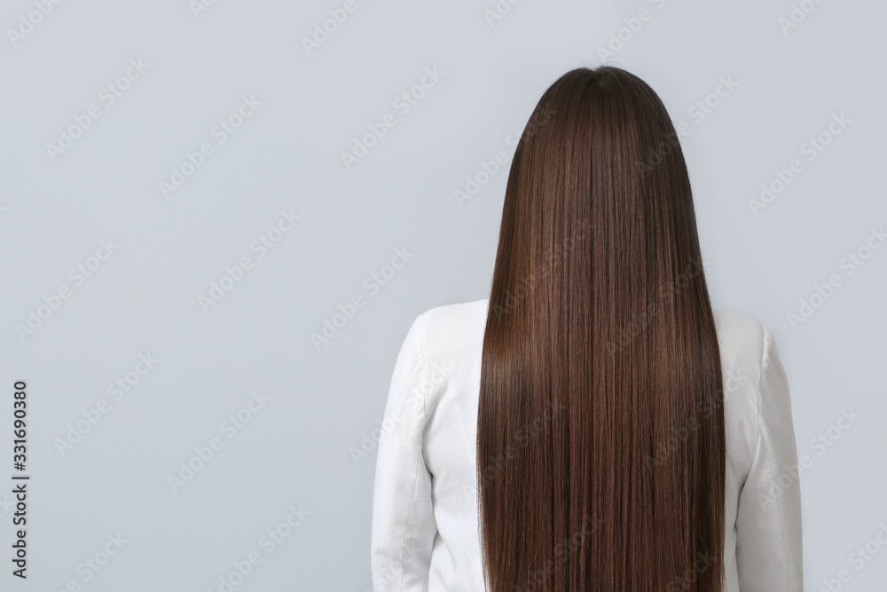 Fototapeta Young woman with beautiful straight hair on grey background