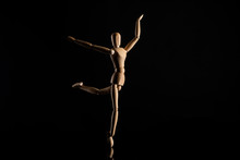 Wooden Doll Imitating Dancing On Black