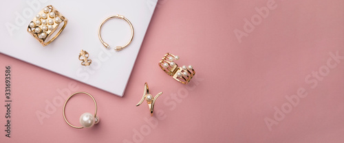 Top view of golden with pearl bracelets on pink and white background with copy space