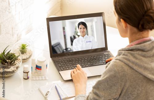 Fotomural Woman sitting at home during an online consultation with her general practitioner