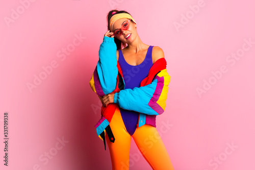 Obraz Back in time 90s 80s. Stylish girl in retro colourful  vintage coat, orange leggings, and purple body, fashion trends, entertainment. 80's Fashion woman over pink background. Beautiful athletic girl. - fototapety do salonu