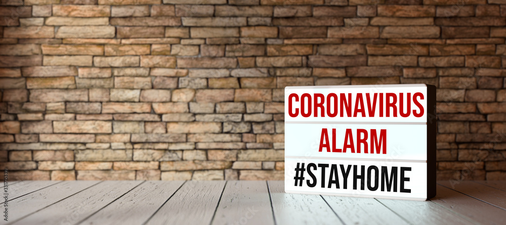 Fototapeta lightbox with text CORONAVIRUS ALARM #STAYHOME in front of a brick wall on wooden floor
