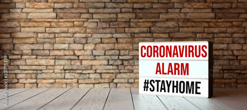 lightbox with text CORONAVIRUS ALARM #STAYHOME in front of a brick wall on wooden floor