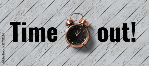 Tela clock on wooden background with message TIME OUT