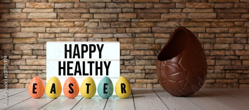 Fototapeta easter eggs with message HAPPY HEALTHY EASTER with big chocolate egg in front of a brick wall obraz