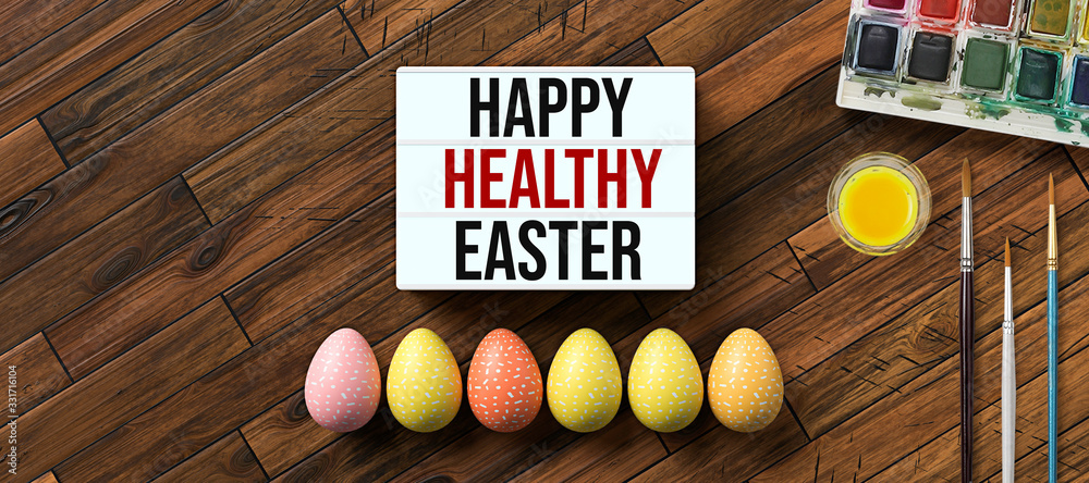 Fototapeta easter eggs with message HAPPY HEALTHY EASTER surrounded by brushes and water color boxes on wooden background