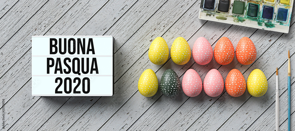 Fototapeta easter eggs with message HAPPY EASTER 2020 in Italian and lightbox with number 2020 surrounded by brushes and water color boxes on wooden background