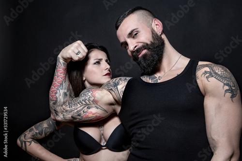 Fotografie, Tablou ragazzo tatuato ci fa vedere il bicipite con la sua ragazza che lo gurda, isolat