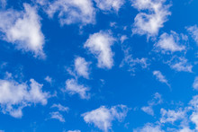 A Few Small Clouds In A Clear Blue Sky. Summer Bright Image Of The Sky.