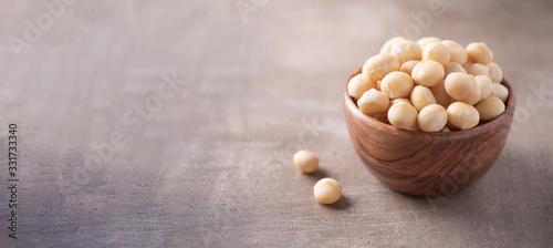 Fototapeta Macadamia nuts in wooden bowl on wood textured background. Copy space. Superfood, vegan, vegetarian food concept. Macro of macadamia nut texture, selective focus. Healthy snack. obraz