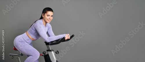 A beautiful athletic young brunette woman in sportswear trains on a sycle in ...