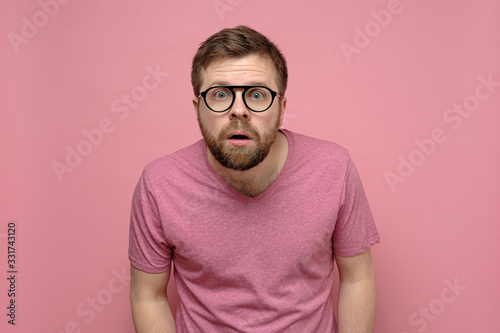 Fotografía Man with glasses is confused, he leaned forward, looks with a shocked expression on his face and does not believe what he saw