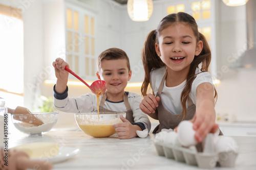 Fototapeta Cute little children cooking dough together in kitchen obraz
