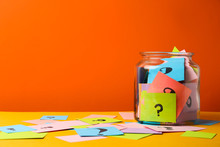 Colorful Cards With Question Marks In Glass Jar On Orange Background. Space For Text