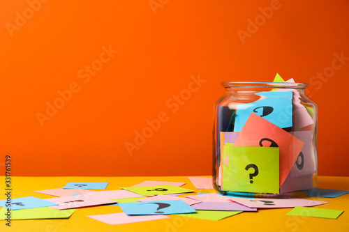 Fototapeta Colorful cards with question marks in glass jar on orange background