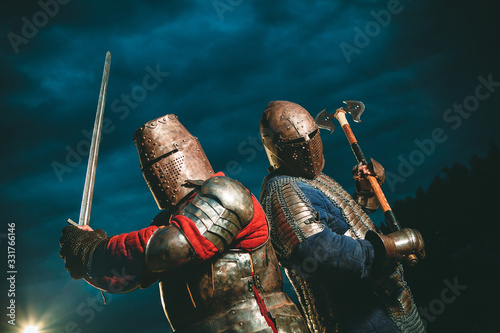 Obraz Two Medieval knights armed with axe and sword. - fototapety do salonu