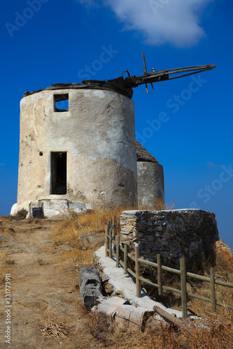 Vivlos, Naxos / Greece - August 25, 2014: Traditional windmill at the mountain village Vivlos, Naxos, Cyclades Islands, Greece