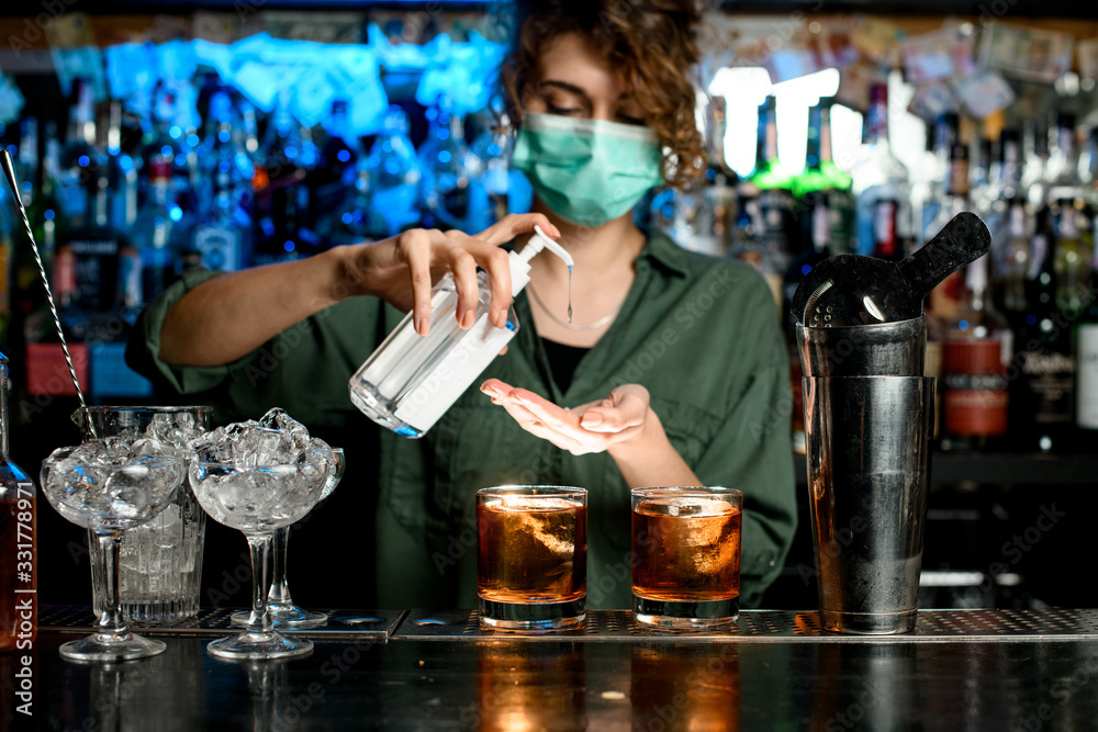 Fototapeta Woman bartender in medical mask treats her hands with disinfector