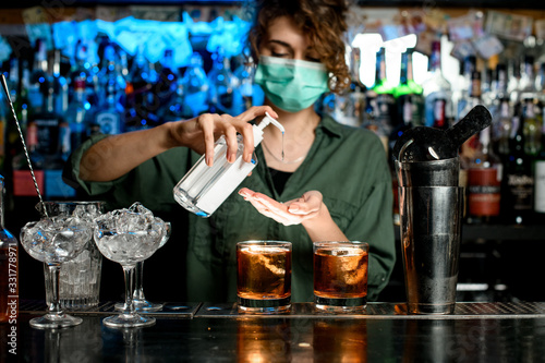 Obraz Woman bartender in medical mask treats her hands with disinfector - fototapety do salonu