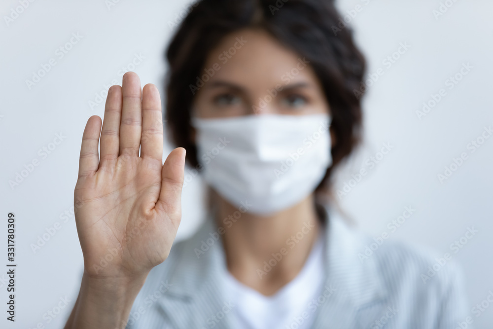 Fototapeta Help stop spreading globally corona virus pandemic infectious disease outbreak. On background woman in mask focus on stretched hand as symbol of keep distance avoid communication, healthcare concept