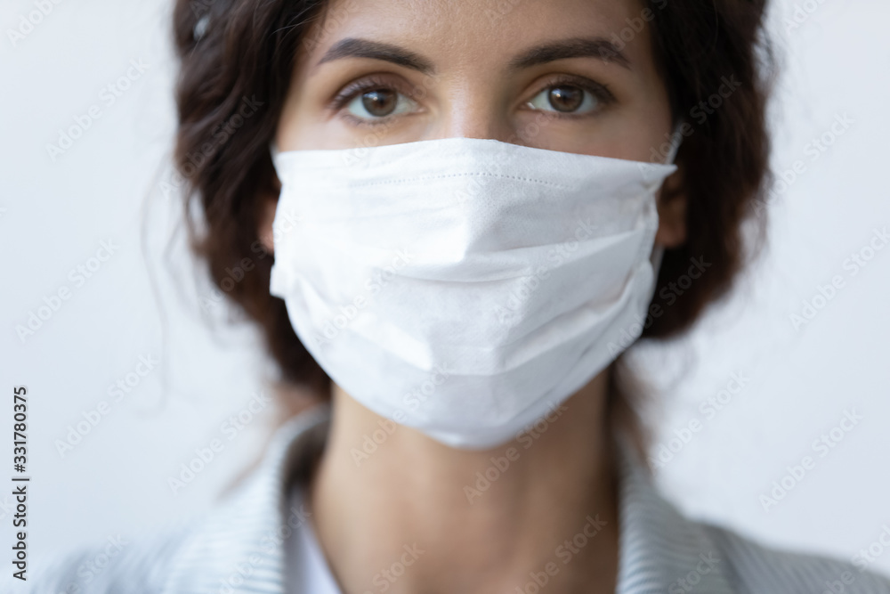Fototapeta Close up portrait of beautiful 30s young millennial woman cover her face wearing facial medical blue mask, anti-coronavirus COVID-19 pandemic infectious disease outbreak protection, healthcare concept