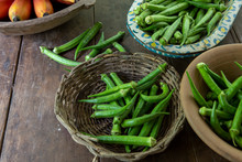 Portion Of Freshly Picked Okra Over Bowls Of Different Materials