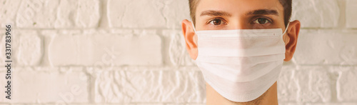 Obraz Banner panorama of young professional doctor wearing face mask for protection against coronavirus COVID-19 with copy space. Confident medic surgeon in protective medical face mask. Preventive measures - fototapety do salonu