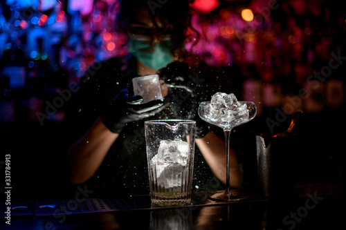 Obraz Close-up. Woman barman in medical mask and black gloves with special device breaks pieces of ice. - fototapety do salonu