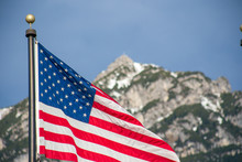 Wawing American Flag Against Mountains Of Rocks And Blue Sky
