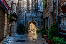 A Narrow Small Street And The Fortification Wall In The Old Medieval Center Of A French Town In The Morning After Rain (Vence, France)