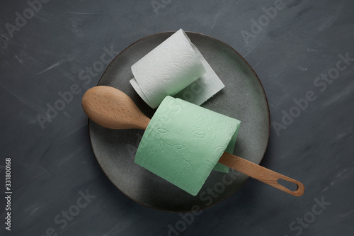 Wooden spoon and rolls of toilet paper on a gray plate Canvas-taulu