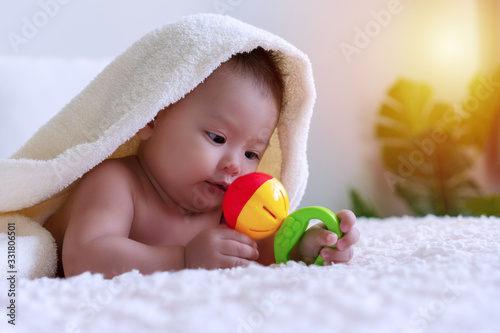Fotografiet Cheerful cute baby lying on bed under white blanket looking at his color toy