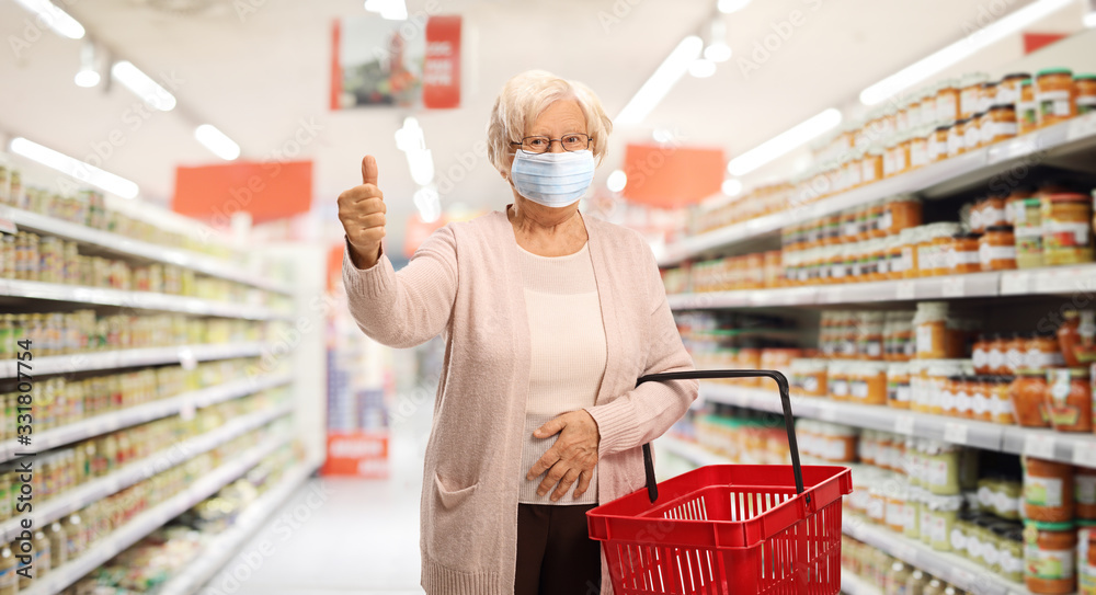 Fototapeta Elderly woman shopping in a supermarket with a protective face mask showing thumbs up