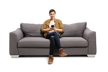 Happy Young Man Sitting On A Gray Sofa And Typing On A Mobile Phone