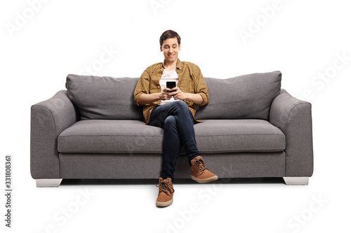 Obraz Happy young man sitting on a gray sofa and typing on a mobile phone - fototapety do salonu
