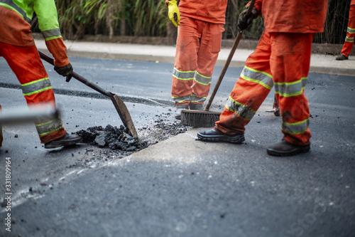 Photo Workers sweeping asphalt