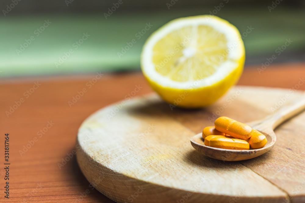 Fototapeta Slice of lemon and vitamin C pills in the wooden spoon on the table