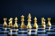 Gold Chess Pieces On Chessboar...