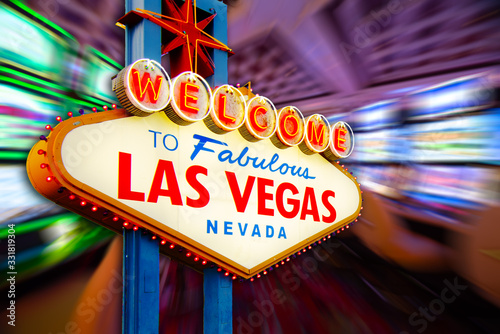 Photo Welcome to Never Sleep city Las Vegas, Nevada Sign with the casino slot machines in blur background