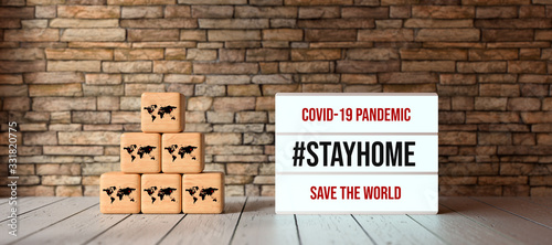 Obraz lightbox with message COVID-19 PANDEMIC #STAYHOME and cubes with world map symbols in front of brick wall on wooden floor - fototapety do salonu