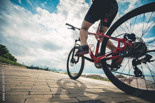Fotografie, Obraz Hands free cycling woman riding Mountain Bike on sunrise seaside