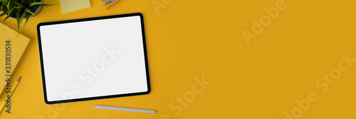 Obraz Cropped shot of blank screen tablet with stylus and stationery on yellow background - fototapety do salonu