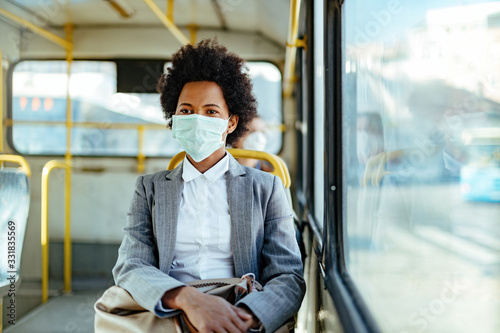 African American businesswoman with face mask for virus protection while commuting by bus Fototapet