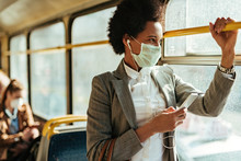African American Businesswoman With Face Mask Texting On The Phone While Traveling By Bus.