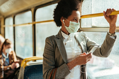 Fotografía African American businesswoman with face mask texting on the phone while traveling by bus