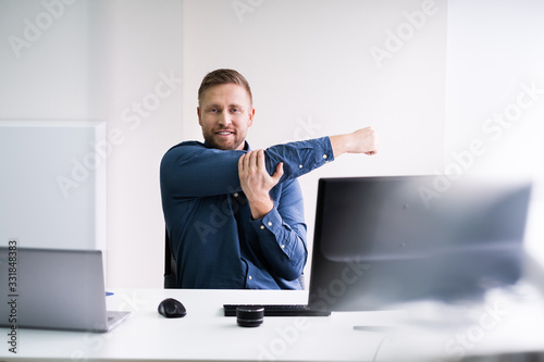 Close-up Of Businessman Stretching His Hands At Workplace Fototapete